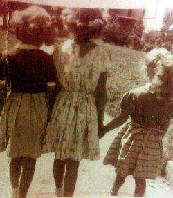 three girls in front of childhood home.