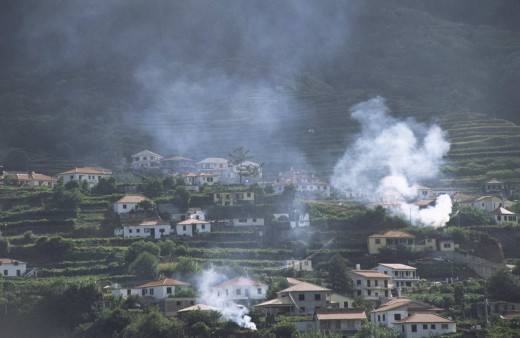 Morning light falling on the smoke drifting from bonfires on the agricultural terraces in Madeira.