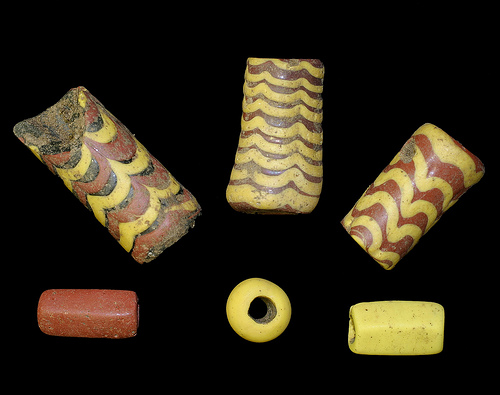 Cylindrical beads. The red and yellow ones, bottom right and bottom left, are pentagonal. The beads were found in Saxon graves at Cliffs End.