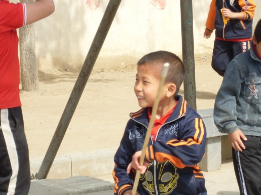 A young boy at the Kung Fu school playing with a stick.
