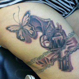 Small revolver and butterfly in ribbon garter