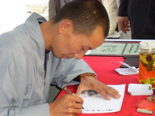 A Shaolin novice monk writing someone's name in Chinese.