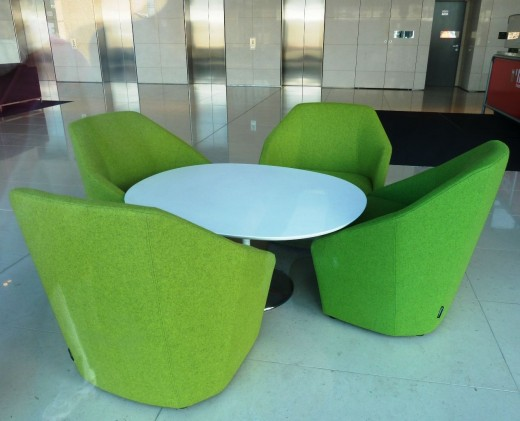 green chairs arranged round a table in a foyer