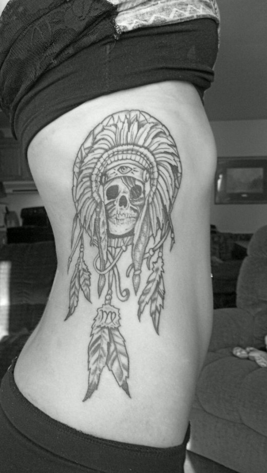 Tribal skull tattoo in someone's ribcage.  Aztec or Mayan head dress?  Source: http://taboo-tattoo.tumblr.com/post/38601361180