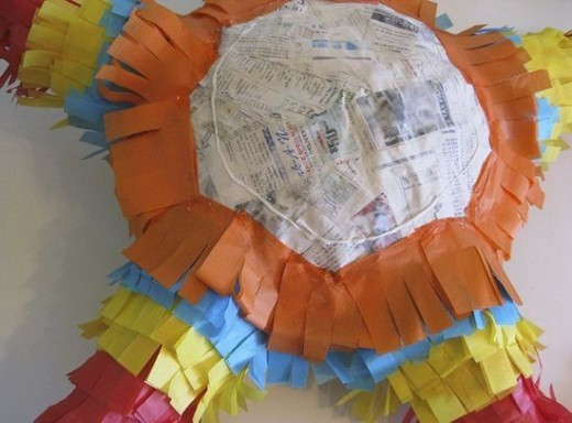 Covering the back of the pinata with colored tissue paper.