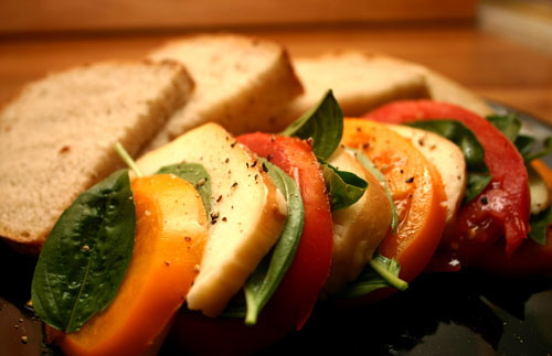 Insalata Caprese, a tomato salad made with basil, fresh mozzarella cheese, and olive oil, here prepared alternately with yellow tomatoes and smoked mozzarella.