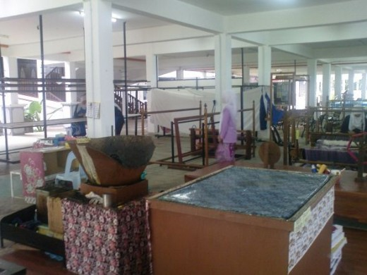A batik chop workplace. You can see the table for stamping the batik. The blacked pot there is where the wax is boiled in order to facilitate the stamping of pattern onto the white cloth.