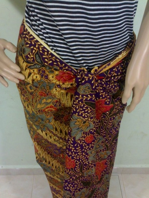 Tucking the end of a batik sarong side securely at the waist.
