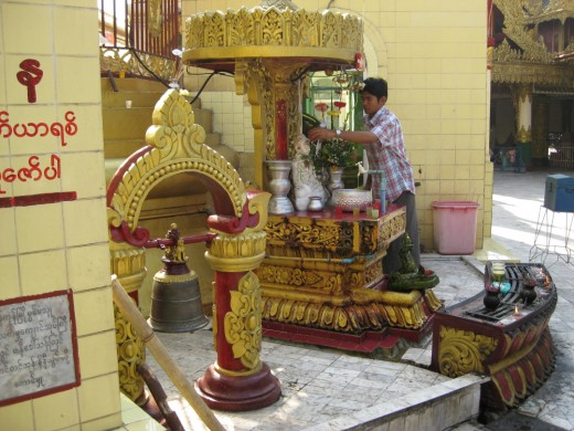 A devotee pours water over an image. This custom is seen as another way of paying respect to Lord Buddha.