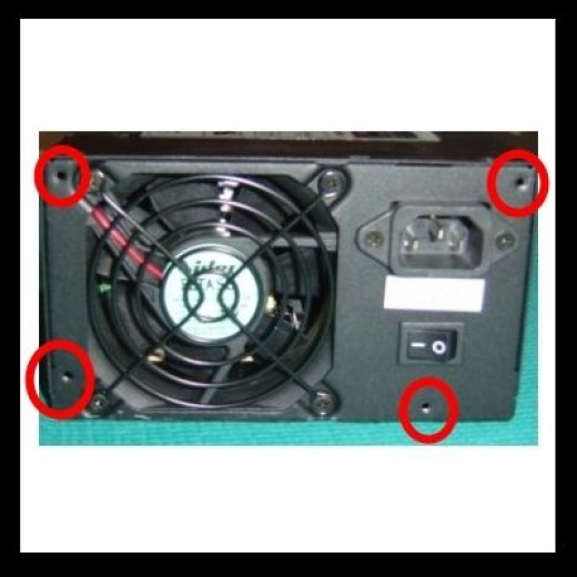 Photo of a Power Supply the way it usually appears at the back of a PC. The power cord has been removed. The four red circles indicate the typical location of the four mounting screws used to secure a power supply.