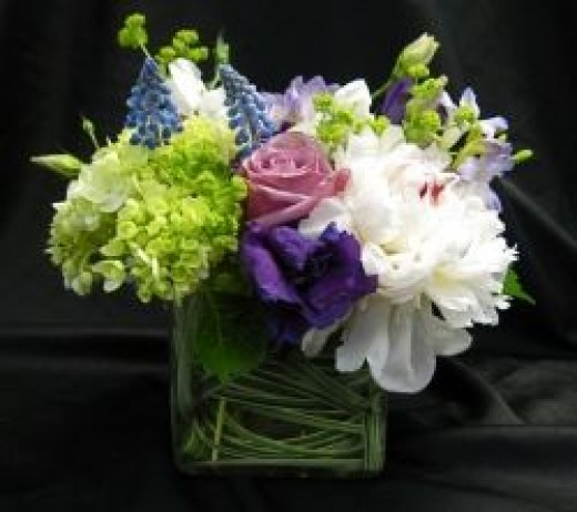 """To order an arrangement like this, ask for  """"a low, compact arrangement in lavenders, purples, white and lime green in a small, clear, glass cube with a leaf wrap inside it."""""""