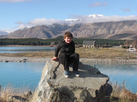 My son sitting on a rock with the Good Shephard church in the background.
