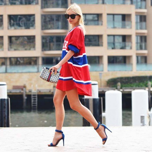 This fashionable woman takes sexy to another level in her street clothing as she flaunts a red and blue sports jersey with blue stilettos with straps.