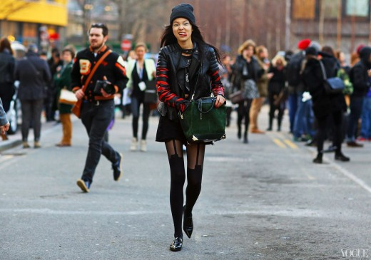 She is wearing see through black stockings with a green handbag and a hat. This is trendy street style.