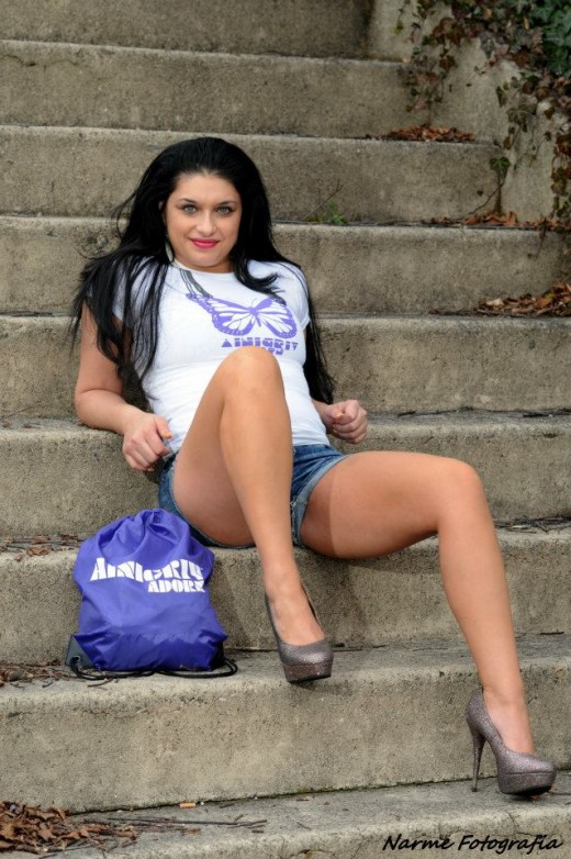 Pretty women wearing urban clothing, Daisy Duke short shorts, high grade stilettos and a tee shirt with butterfly topped off with sporty handbag.