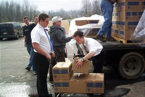 Missionaries from the Arkansas Little Rock Mission help unload supplies sent by the LDS Church to help local children.