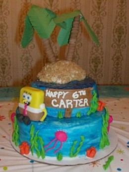 """Tiered cake with just a carved """"island"""" and a fondant covered cake Spongebob."""