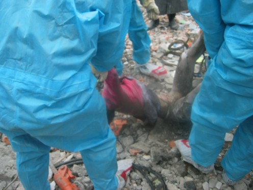 Volunteers, untrained, unconcerned about their personal safety, pulls a body from the rubble.