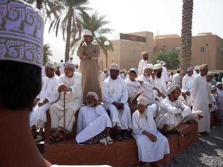 Oman men watching the market transactions