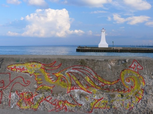 Two Sentinels shows a retaining wall on a pier with dragon graffiti and a lighthouse on the opposite side of the channel.