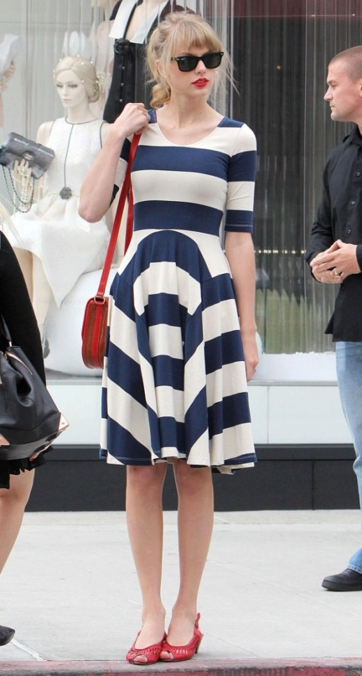 Taylor Swift wearing striped dress and Raybans