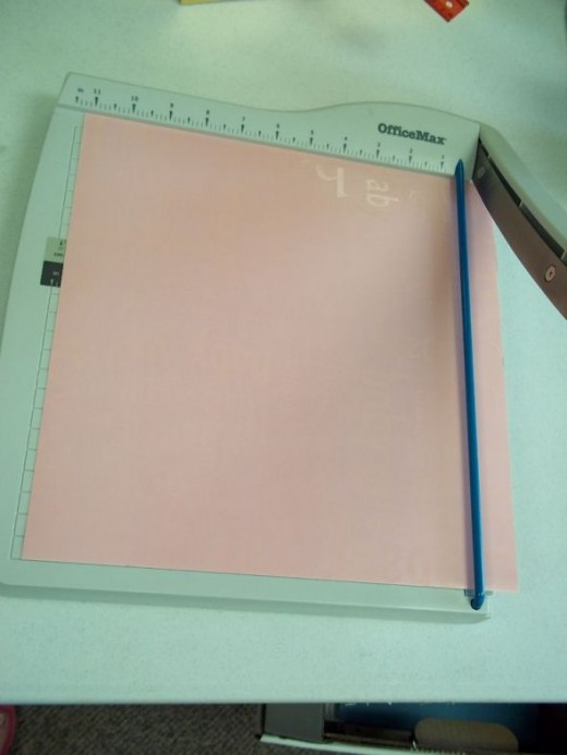 "Cut a piece of scrapbooking paper to fit. If your base is longer or wider than 12"", you might need two pieces."