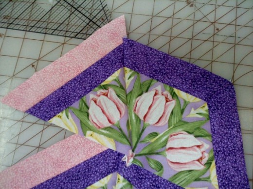 Next I sewed a pink-trimmed triangle to the set of two, then another.