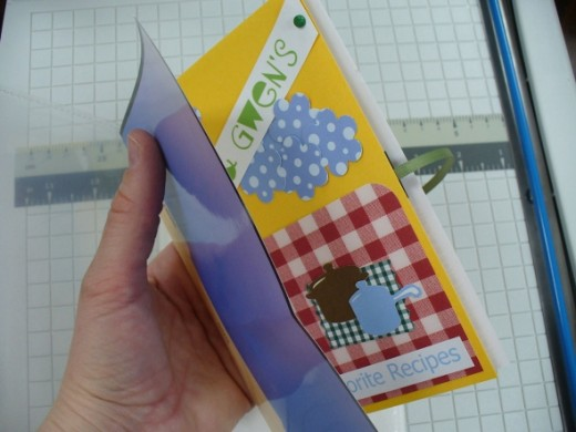 When you're sliding layered artwork into a sleeve, a slide jig will help you keep the fine details and embellishments from getting caught, ripped, and ruined.  Really, all this jig consists of is some scrap paper folded over your artwork.  You'll sli