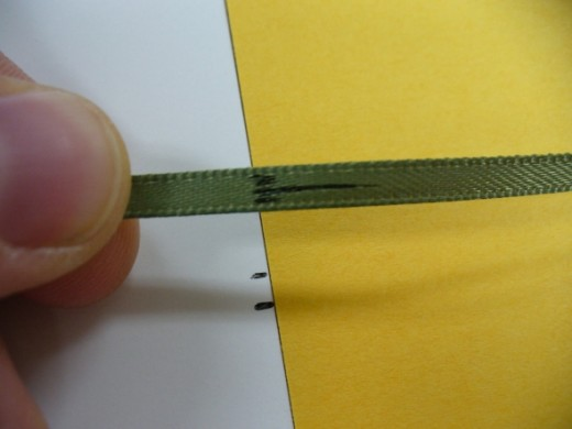 This shows the short end of the ribbon lined up to be taped down and hidden under the cover artwork.  The marks help remind me how to place it so I don't make frustrating mistakes.