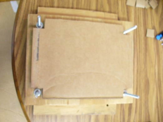 Start by layering the bottom of the press with one piece of cardboard.