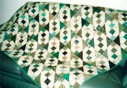 Margaret's Uncle John loves his scrap quilt in his favourite greens