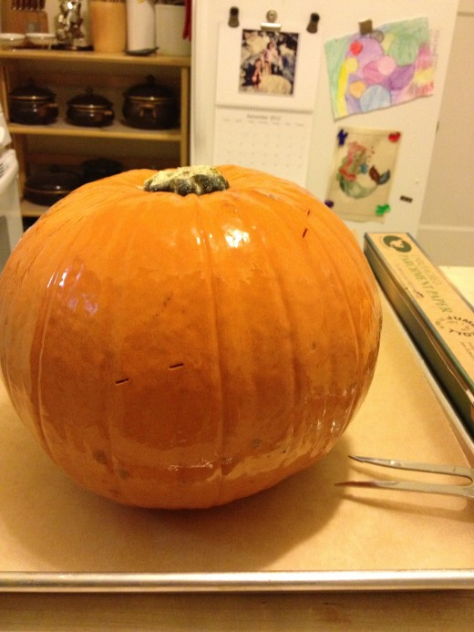 Sugar pie pumpkin, oiled and pricked with meat fork, ready to roast