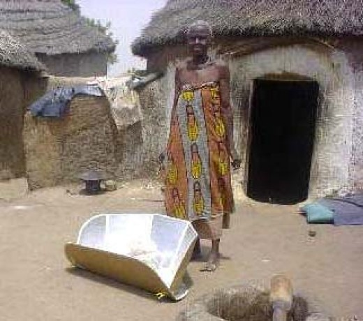 A solar oven (otherwise known as a solar cooker) being used outside a hut in Africa for cooking food