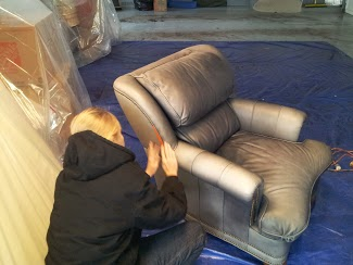 Technicians prep the leather and cover any decorativ tacking or woodwork before the leather is dyed