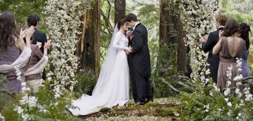 Edward and Bella kiss against the beautiful backdrop of flowers.
