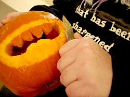 Mythphile wearing the pointy Unicorn shirt, while carving up a pumpkin
