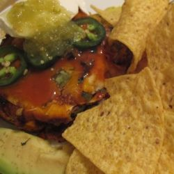A serving of wet burritos with Frank's Red Hot Sauce, salsa verde, sour cream, avocado, jalapenos and tortilla chips.