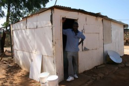 Amos at the door of the shack in Mamelodi which he shares with Gracious, their toddler, and Mercy