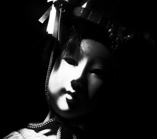 A quietly staring doll can be terrifying in a shadowy room.