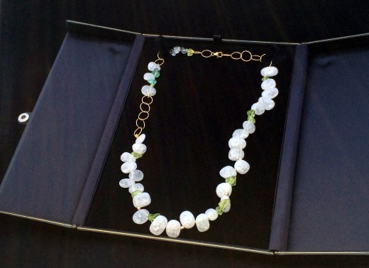 A properly stored crackle quartz necklace.  The box's tabs keep beads from knocking together. Photo courtesy Naiad Necklaces.