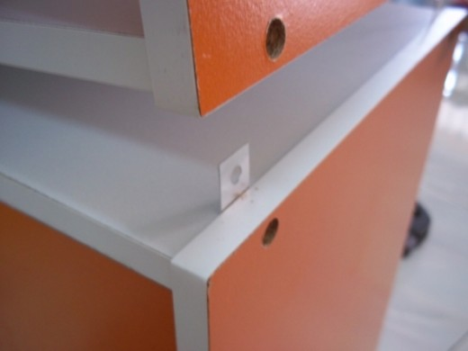 The 2 hole flat connector is now secured at the lower storage shelf.