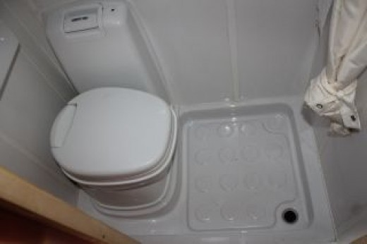 Toilet and shower tray, the basin is folder up left above toilet and folds down for use