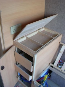 The small cupboard  above the water heater, showing drawers and top tray, the TV sits on this.