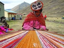 A woman weaves on her back-strap loom in the remote high mountain community of Chuallacocha - located above the Sacred Valley.