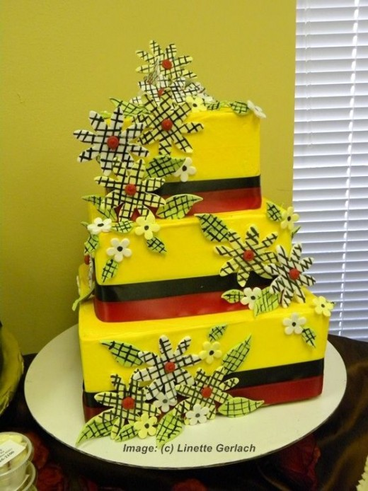 yellow cake with red and black ribbon