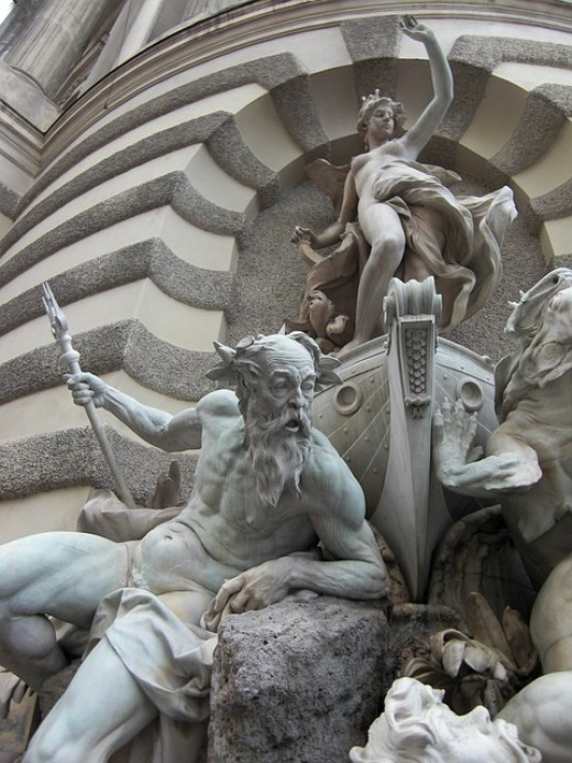 Figure of Neptune, the Roman god of freshwater and the sea, at a fountain in Vienna, Austria.  He holds a trident in his right hand, the three-pronged fork that would become the astronomical symbol for the planet Neptune.