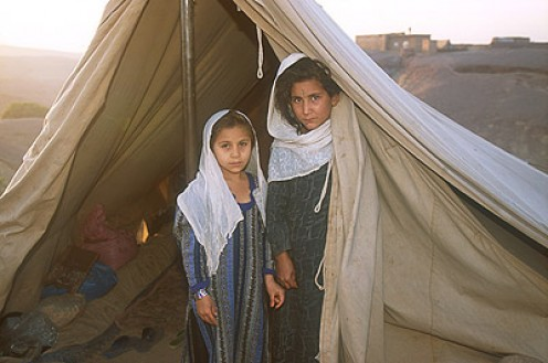 Two Afghan girls living in a tent in a refugee camp. It shows how the living conditions have declined in the country during the war.