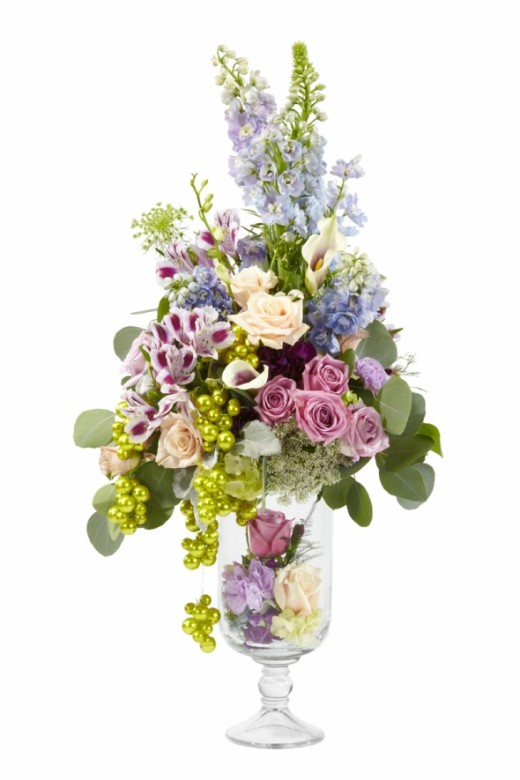 More traditional arrangement in lovely soft, pastel colors. The flowers can be arrange in foam or a bouquet holder placed in the neck of the vase. The base is filed with flower heads and the whole it trimmed with mega beaded wire in lime green to add