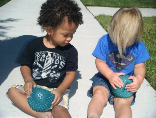 These two preschoolers are actually cousins enjoying their learning together through the exploration of round, bumpy, and squishable balls.