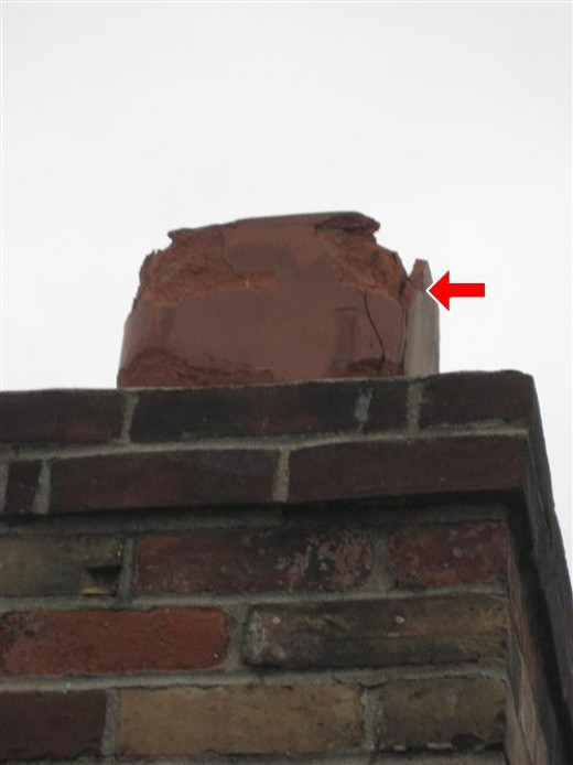 Damaged flue tile on masonry chimney will require replacement.